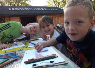 Lara, Mia und Adrian sind gut gelaunt. Sie malen Heißluftballons.