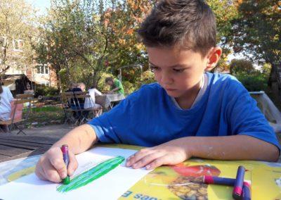 11 Nevio malt seinen Zeppelin mit grünen und blauen Wachspastellkreiden an.