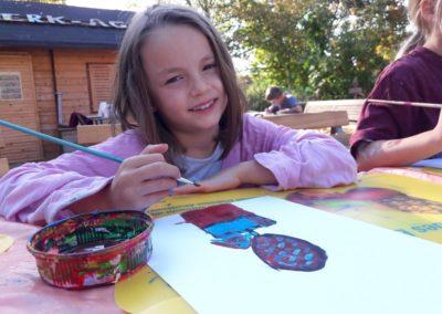 Mila malt mit Acrylfarben einen Heißluftballon. In dem Korb des Heißluftballons sitzt ein Mädchen.