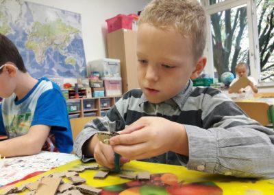 36 Hier sieht man Adrian, der aus einer großen Pappe kleine Pappstücke schneidet. Die brauchen wir, um einen 3D-Effekt auf dem Wimmel-Himmel herzustellen. 3D bedeutet dreidimensional. Wenn man etwas in 3D sieht, dann kann man die Höhe, die Breite und die Tiefe von Figuren sehen.
