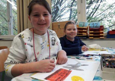 """Lilian und Martha haben gute Ideen. Lilian malt ein Flugzeug mit Werbebanner. Darauf steht: """"Die Köllerholzschule ist cool! Wir machen tolle Sachen!"""""""