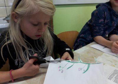 Lilli schneidet gerade ihre gemalte Blume aus.