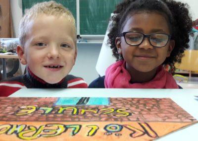 Adrian und Amina sitzen vor der fliegenden Köllerholzschule.