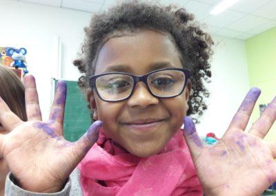 Hier sieht man Amina mit lilafarbenen Ölkreidefingern. Amina macht das Malen mit Ölkreide besonders viel Freude.