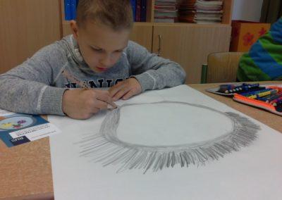 Luka zeichnet eine große Lupe auf seinen Kopf.