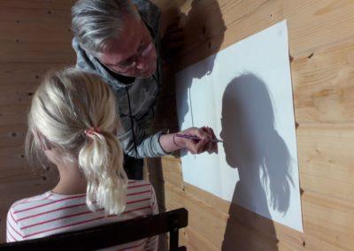 024 Das ist Lea. Beim Zeichnen muss sie ganz ruhig sitzen, damit Herr Menzler den Umriss ihres Kopfes aufzeichnen kann.