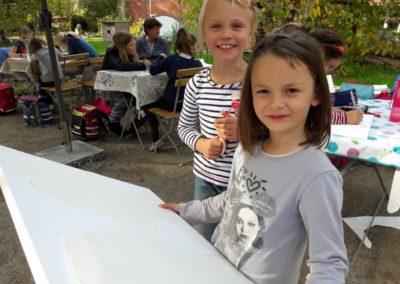 031 Als nächstes suchen wir uns eine Leinwand aus. Stella und Mila legen die ausgeschnittenen Köpfe auf die Leinwand.