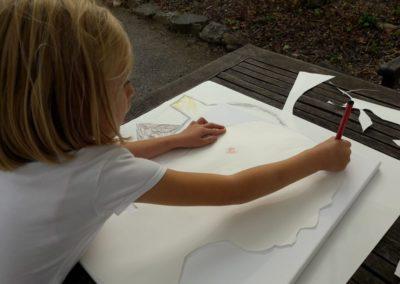 Linda zeichnet jetzt den Umriss ihres Kopfes noch einmal auf die Leinwand.