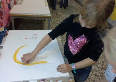 Anna malt ihre Haare mit Ölkreide auf die Leinwand.
