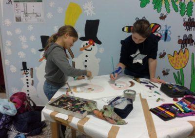 Johanna und Lillian malen gerade auf ihrem Gefühlebild mit Aquarellfarben.