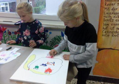Pia und Mia benutzen für ihr Bild Ölkreiden und Pastellkreiden.