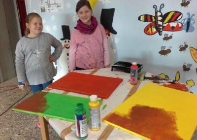 Martha und Lilian malen nun weitere Leinwände in grün, rot und gelb an.