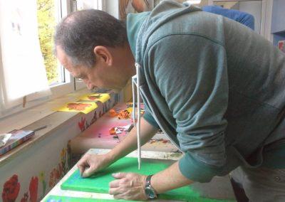 093 Unser Schulleiter Herr Vielhaber hilft uns immer gerne. Er schreibt in ordentlicher Schrift die Namen aller Kinder und die Titel der Bilder auf die Leinwände.